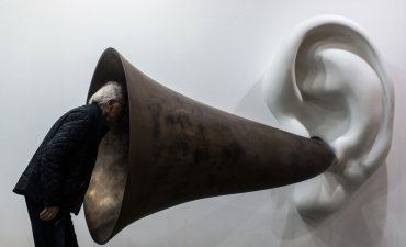 "A visitor peering into John Baldessari's ""Beethoven's Trumpet (With Ear)"